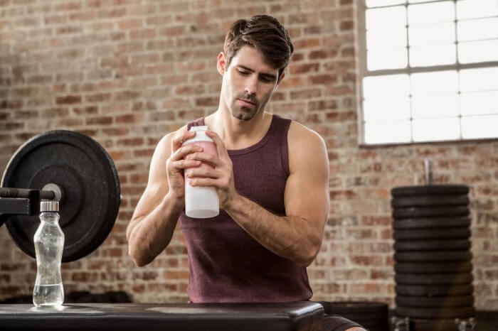 man making a protein shake at the gym