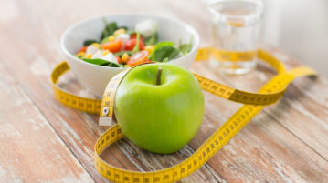 close up of green apple and measuring tape