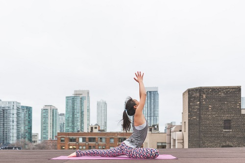 woman doing yoga at the rooftop