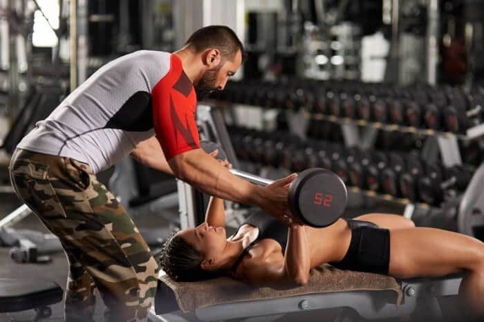 man working out lifting weights with helper