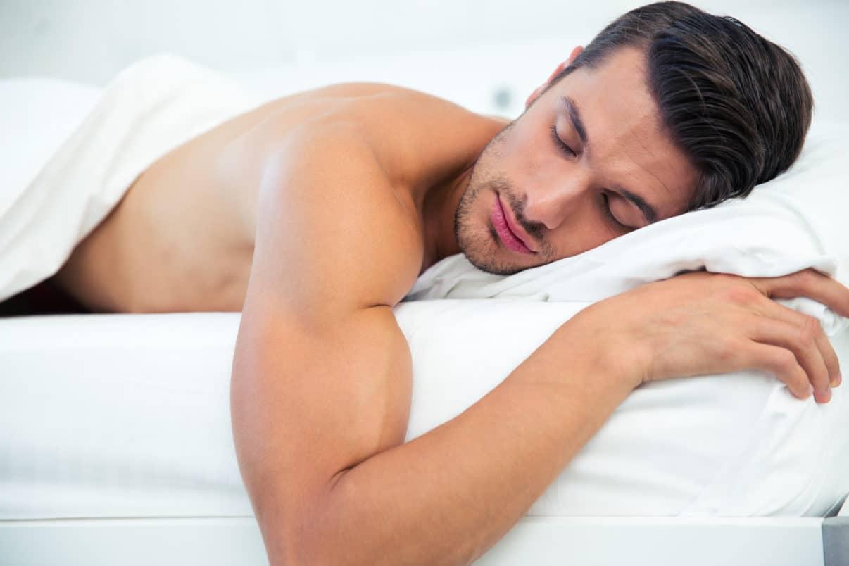 Bodybuilder sleeping in bed
