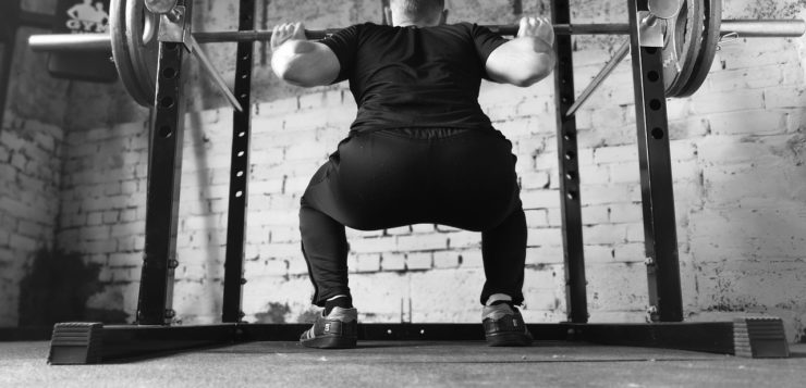 Black and white photo of a man doing squats