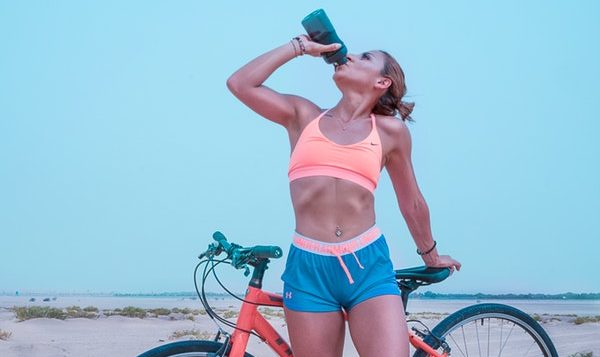woman drinking beside bike